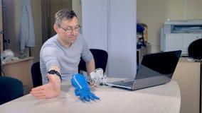 En tekniker undervisar en bionisk handprototyp att göra en näve stock video