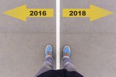 2016 en 2018 tekstpijlen op asfaltgrond, voeten en schoenen op F Stock Afbeelding