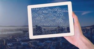 En tenant le comprimé et la ville avec le nuage téléchargez les icônes Photographie stock libre de droits