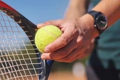 En tennisspelare som rymmer racket och bollen i händer fotografering för bildbyråer