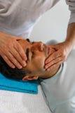 En terapeut applicerar hans händer på framsidan av en patient Royaltyfria Foton