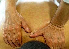 En terapeut ger en massage på övrebaksidan av hans patient royaltyfri foto
