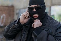 En terrorist, en bandit i ett svartläderomslag och en maskering som talar på telefonen royaltyfri bild