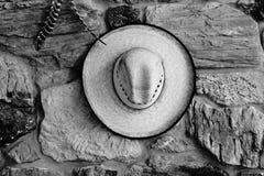 En Texas cowboyhatt som hänger på spisen i svartvitt royaltyfri fotografi