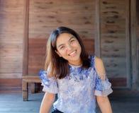 En thailändsk flicka som ler på hennes wood hem Arkivfoto