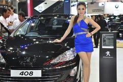 En thailändsk kvinnligpresentatör bredvid en Peugeot 408 Arkivfoton