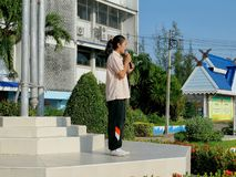 En thailändsk studentgilr talar till deras vänner, när de skulle ställa upp för att respektera till nationsflaggan i morgonen på royaltyfria foton