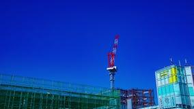 En tidschackningsperiod av rörande kranar bak den blåa himlen på under-konstruktionen i Tokyo det breda skottet stock video