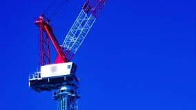 En tidschackningsperiod av rörande kranar bak den blåa himlen på under-konstruktionscloseupzoomen arkivfilmer