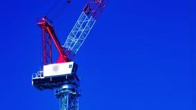 En tidschackningsperiod av rörande kranar bak den blåa himlen på under-konstruktionscloseupzoomen stock video