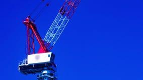 En tidschackningsperiod av rörande kranar bak den blåa himlen på under-panorera för konstruktionscloseup stock video