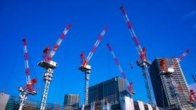 En tidschackningsperiod av r?rande kranar p? under-konstruktionen i Tokyo bred skjuten lutande stock video