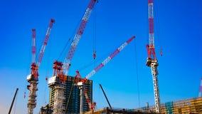 En tidschackningsperiod av r?rande kranar p? under-konstruktionen i Tokyo den breda sk?t zoomen arkivfilmer