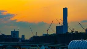En tidschackningsperiod av r?rande kranar p? under-konstruktionen i Tokyo p? den breda sk?t zoomen f?r skymning lager videofilmer