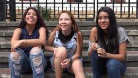 En tienermeisjes die luisteren lachen stock videobeelden