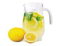 En tillbringare av lemonad med den nya mintkaramellen och ljusa gula citroner Ny lemonad med citroner och mintkaramellen som isol Royaltyfria Foton