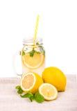 En tillbringare med citronjuice och citroner på ett ljust tyg, på en vit bakgrund Skivor för ett sugrör och citroni en stor krus Royaltyfri Fotografi