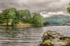 En tillfällig stenbrygga i en sjö, berg och stormmoln arkivbilder