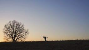 En tillfredsställd bonde dansar ib fältet Kontur av en solnedgång eller en soluppgång i fält arkivfilmer