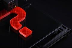 En tillverkning 3D-printer en stor frågefläck från röd plast- i mörker som omger med flott ljust lynne royaltyfri bild