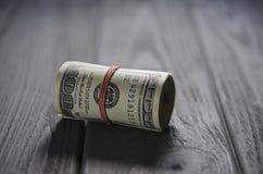 En tjock rulle av hundra dollarsedlar band en röd gummiband ligger på den gråa trätabellen arkivfoton
