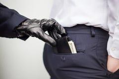 En tjuv tar en plånbok med en kassa från ett fack av en man i ett s arkivfoton