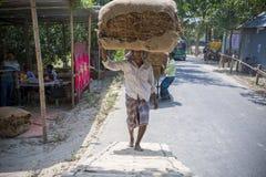 En tobakarbetare som mycket förutom bär av tobak i Dhaka, Vatara, manikganj, Bangladesh Arkivfoton