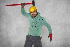 En tokig arbetare slår sig häxan en stor hammare Fotografering för Bildbyråer
