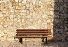 En tom bänk, sten blockerar bakgrund Arkivbild