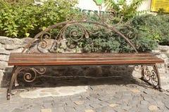 En tom brun bänk med ensemblemetallprydnader Royaltyfria Bilder