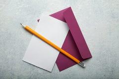 En tom förälskelsebokstav till valentin dag Pappers- rosa kuvert och blyertspenna p? ett vitt tappningskrivbord, utrymme f?r text arkivfoton