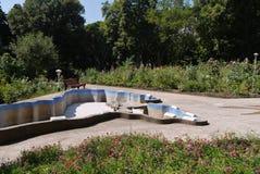 En tom pöl i mitt av en parkera med krokiga bänkar och stora rabatter Royaltyfri Foto