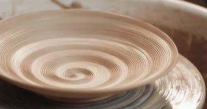En tom platta med lättnad roterar på krukmakerihjulet, slut upp Spolande lerastruktur Handgjort hantverk Vit lera arkivfilmer
