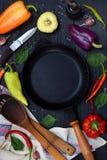En tom svart stekpanna, runt om olika variationer av söta och varma peppar på mörk träbakgrund Förberedelse av ragu eller f Royaltyfria Bilder