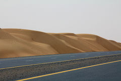 En tom väg bredvid en öken i Dubai, UAE Royaltyfri Foto