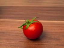 En tomat på trätabellen Royaltyfria Bilder