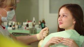 En tonåring berättar doktorn vad tänder gör ont för att göra behandlingen arkivfilmer