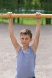 En tonåring i en T-tröja är förlovad i gymnastik på en horisontalstång Arkivbild