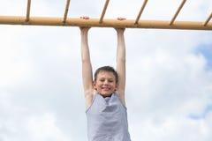 En tonåring i en T-tröja är förlovad i gymnastik på en horisontalstång Arkivfoton