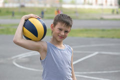 En tonåring i en väst rymmer en boll i hans hand royaltyfri foto