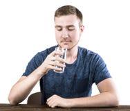 En tonåring i ett mörker - den blåa T-tröja dricker ett exponeringsglas av vatten som isoleras på en vit bakgrund Medicin royaltyfri bild