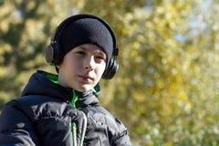 En tonåring i ett svart omslag och på hörlurar som lyssnar till musik på bakgrunden av en höstskog eller, parkerar Royaltyfri Fotografi