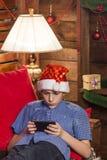 En tonåring i en Santa Claus hatt, i jeans, i en blå skjorta, ligger på en stol med röda kuddar och ser telefonen på det wal Royaltyfri Foto