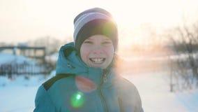 En tonåring i vinter parkerar att le framsidacloseupen Tiden av solnedgången Gå i den öppna luften En sund livsstil stock video