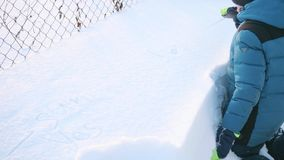 En tonåring i en vinter parkerar målarfärger en istapp i snön Snöig frostig solig dag Skoj i den nya luften lager videofilmer