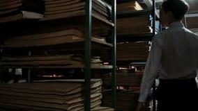 En tonåring i en vit skjorta går mellan bokhyllor med gamla dokument i arkiv som söker för litteratur Källarearkiv r stock video
