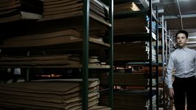 En tonåring i en vit skjorta kör mellan hyllorna med dokument i arkivet r Arkivrum lager videofilmer