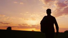 En tonåring med en ryggsäck över hans skuldra går in mot solnedgången i fältet eller i bygden Nytt begrepp - Arkivbild