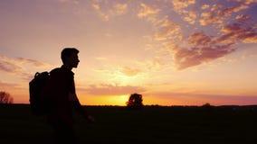 En tonåring med en ryggsäck över hans skuldra går in mot solnedgången i fältet eller i bygden silhouette royaltyfri fotografi