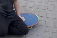 En tonåring med en skateboard Sitter på en skateboard Royaltyfria Foton